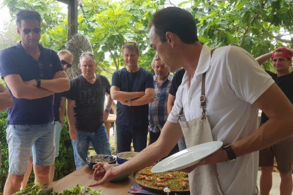 team cooking paella
